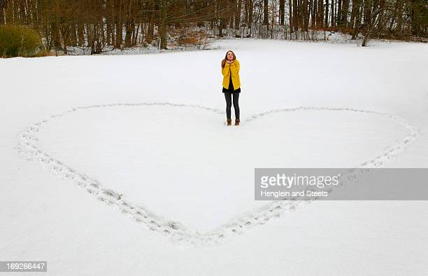 Woman making heart shape in snow