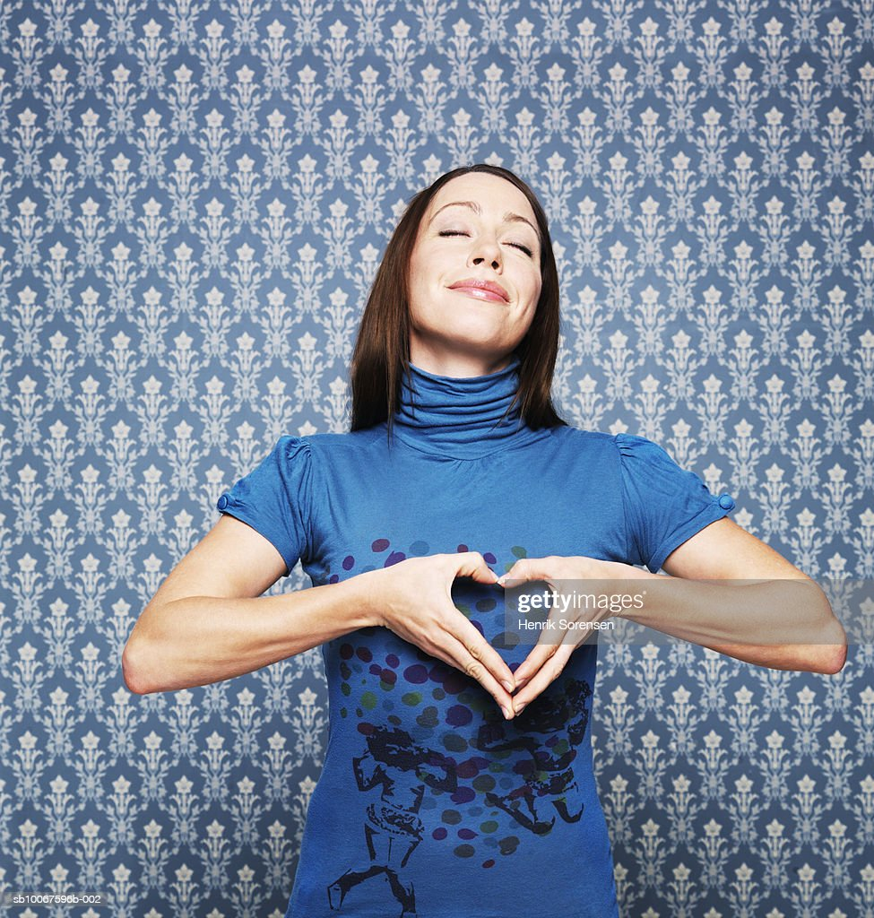 Woman making heart shape with hands : Stock Photo