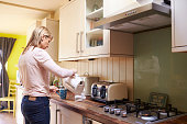 Woman Making Hot Drink In Kitchen Of Stylish Apartment