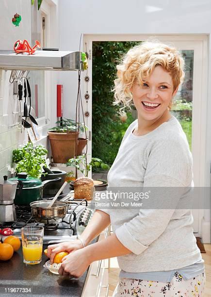 woman making orangejuice for breakfast.