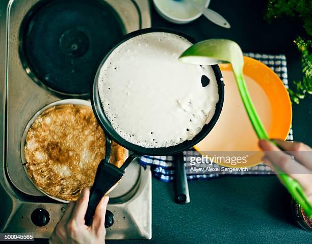 Woman making pancakes in kitchen