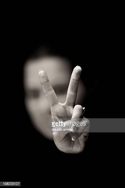 女性手ぶりを Peace サインに黒色の背景