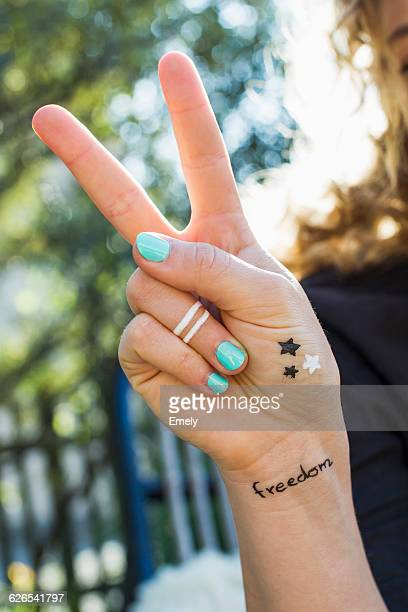 Woman making peace sign with hand