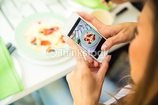Woman making photo of food on smartphone : Stock Photo