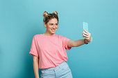 youth trendy woman making photo on her smartphone against a blue pastel background . making cool selfie
