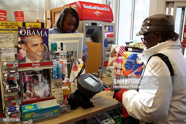 A woman making purchases in a store in the Hyde Park Kenwood district on the counter together with other goods are displayed on sales two magazines...