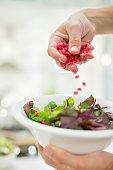 Woman making salad in kitchen