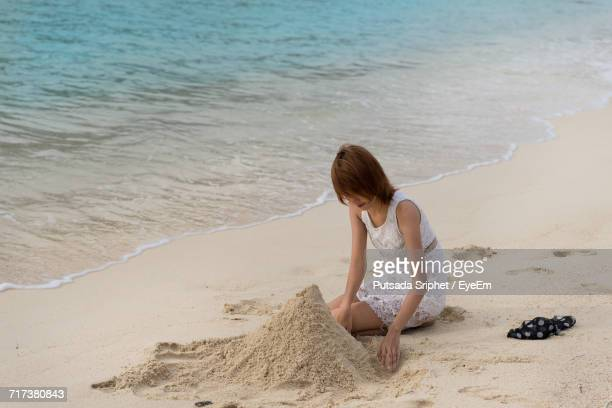 Woman Making Sandcastle At Beach
