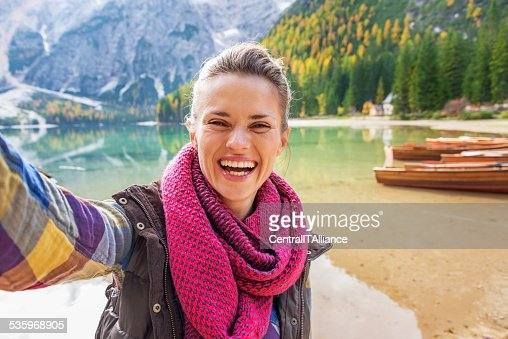 Woman making selfie on lake braies in south tyrol, italy : Stock Photo