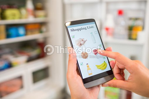 woman making shopping list on phone connected to the refrigerator stock photo