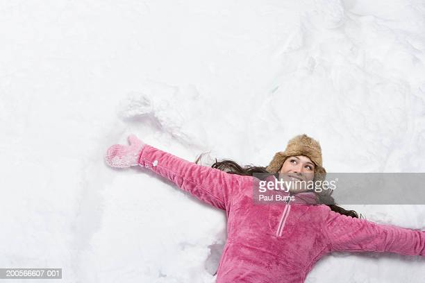 Woman making snow angel smiling