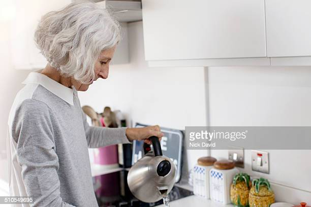 Woman making tea in modern apartment