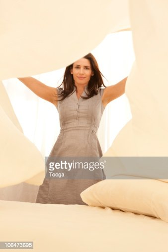Woman making the bed tossing bed sheets   Stock Photo. Woman Making The Bed Tossing Bed Sheets Stock Photo   Getty Images