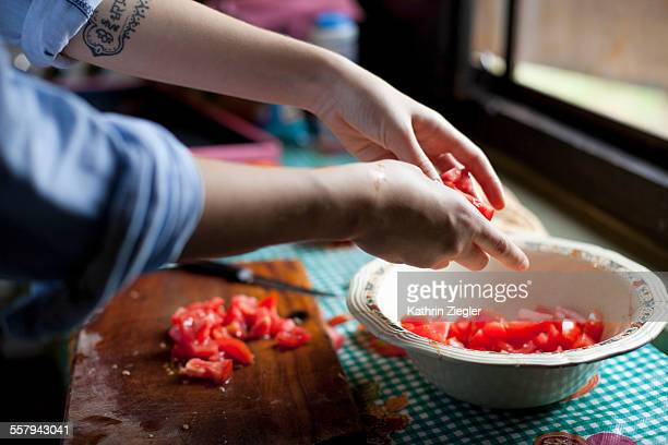 woman making tomato salad, close-up of hands