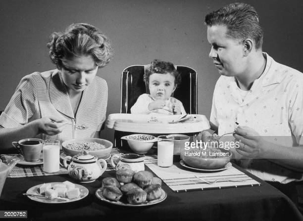 A woman man and a baby in a high chair eat breakfast at a table circa 1950