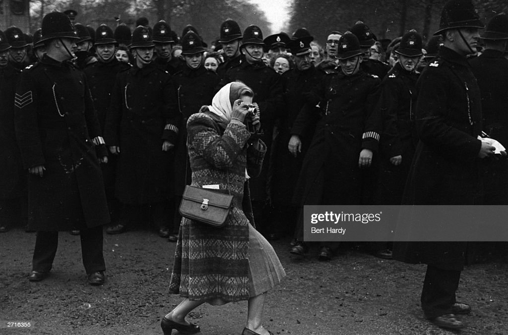 A woman manages to break through the line of policemen to take a photograph, as the crowds wait for a glimpse of the newly married Princess Elizabeth and her husband the Duke of Edinburgh. Original Publication: Picture Post - 4438 - Royal Wedding - pub. 1947