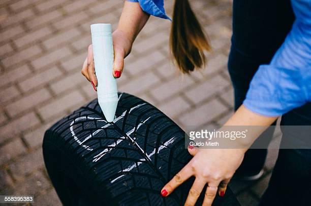 Woman marking car tire