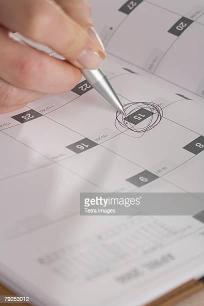 Woman marking day on calendar
