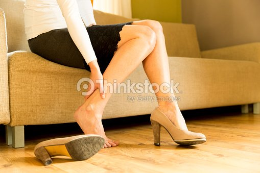 Woman massaging her legs after wearing high heels all day at work in office : Stock Photo