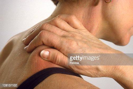 Woman massaging her shoulder blade : Stock Photo