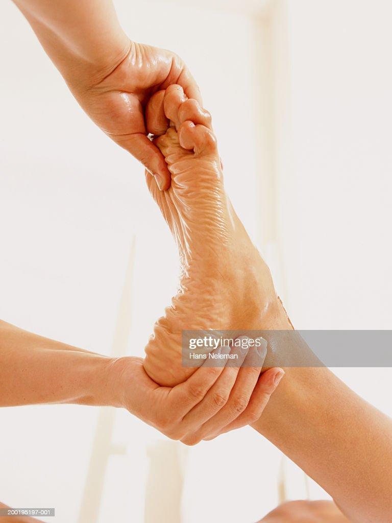 Woman massaging man's foot, close-up : Stock Photo