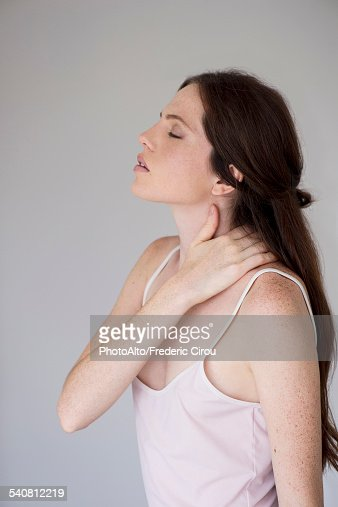 Woman massaging neck, side view