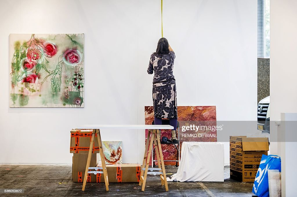 A woman measures a wall during the setting up of the 32nd edition of the KunstRai art fair in Amsterdam, on May 31, 2016. The KunstRai art fair is the longest running art fair for contemporary autonomous and applied art in the Netherlands. / AFP / ANP / Remko de Waal / Netherlands OUT / RESTRICTED