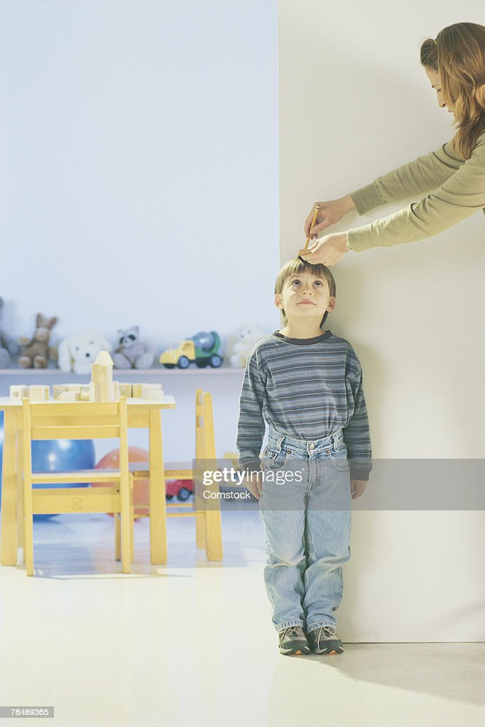 Woman measuring boy's height