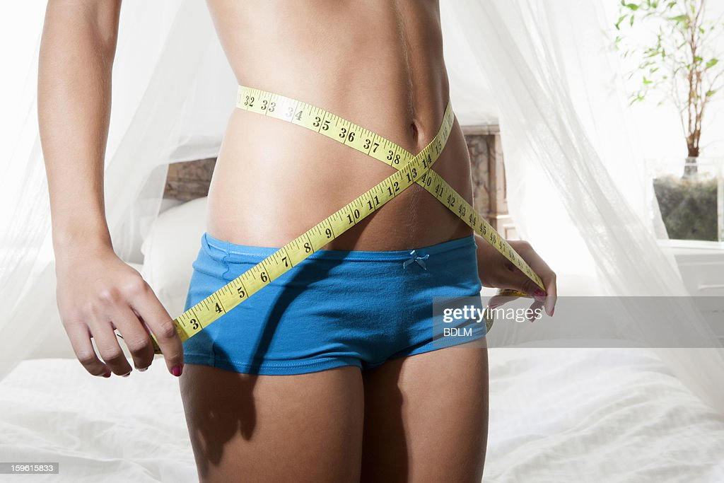 Woman measuring her belly with tape : Stock Photo