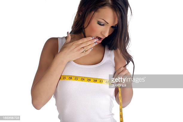 Woman measuring her chest shocked at the size