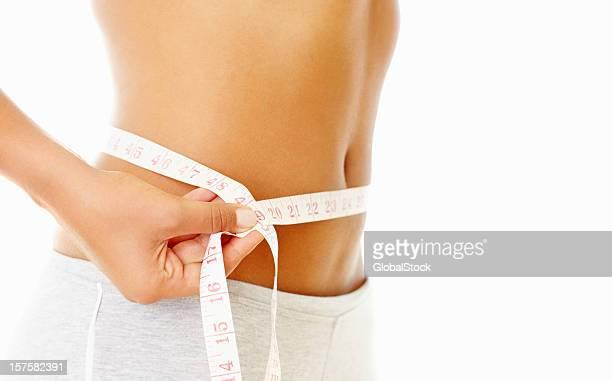 測定女性彼女のスリムなウエストにテープ
