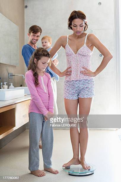 Woman measuring her weight on a weighing scale with her family in bathroom