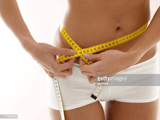 Woman measuring hips with tape measure.