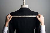 Woman measuring jacket on tailor mannequin.