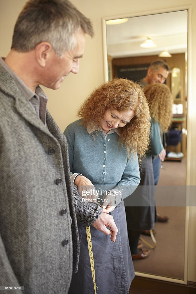 Woman measuring jacket sleeve in clothing shop : Stock Photo