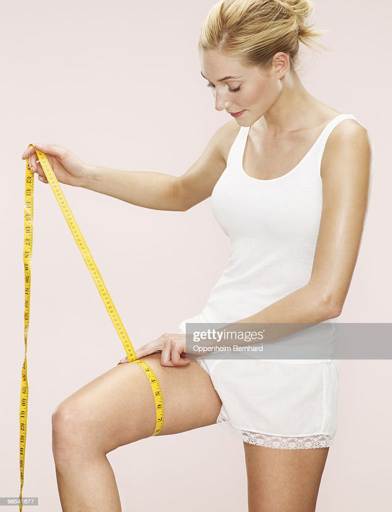 woman measuring size of her thigh : Stock Photo