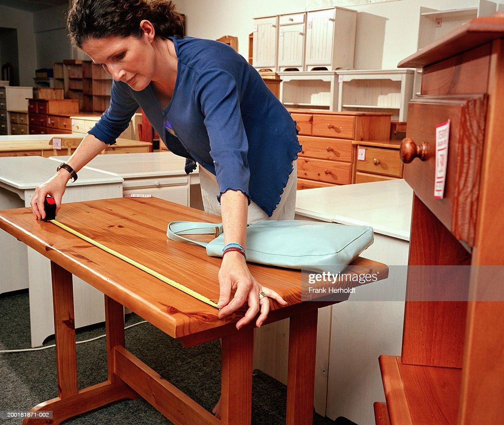 Woman measuring table in furniture shop : Stock Photo