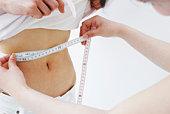 Woman measuring the friend's waist size