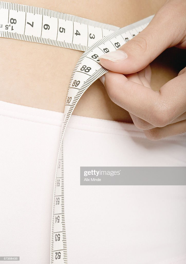 Woman measuring waist, extreme close-up