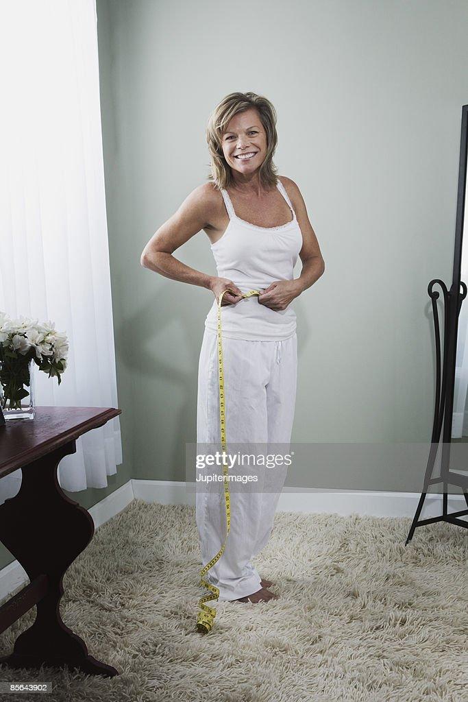 Woman measuring waist : Stock Photo