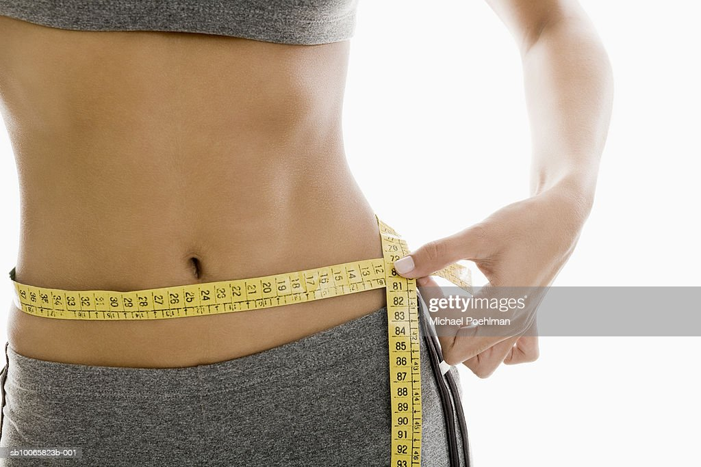 Woman measuring waist using tape measure, mid section : Stock Photo
