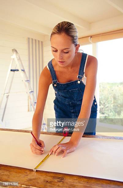 Woman measuring wallpaper