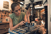 woman mechanic is using a vertical electric dill machine