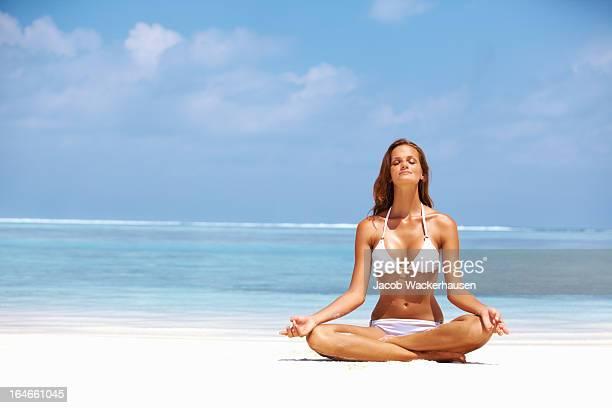 Femme, méditer au bord de la plage