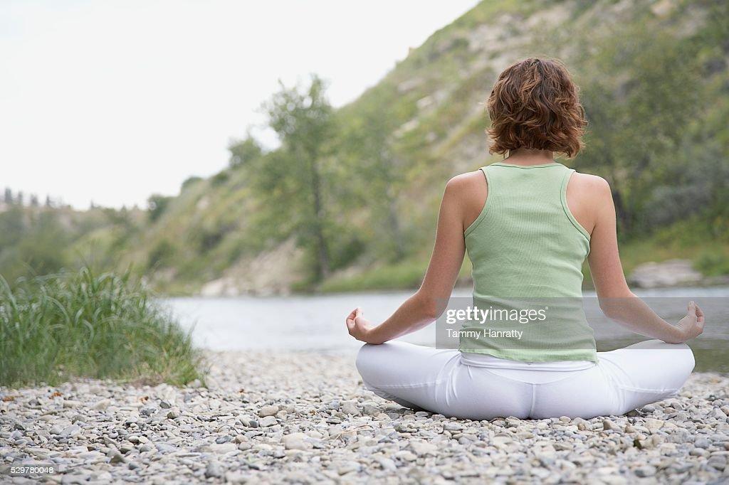 Woman meditating at edge of river : Stock-Foto