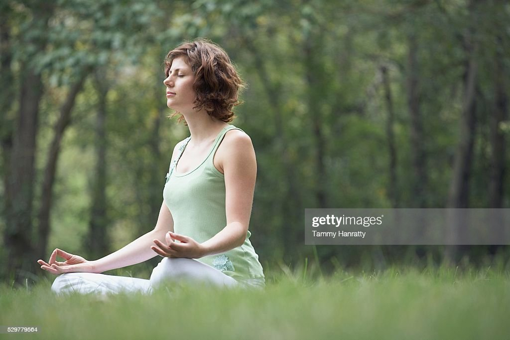 Woman meditating at the park : Stock Photo
