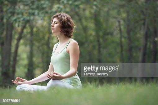 Woman meditating at the park : Stock Photo