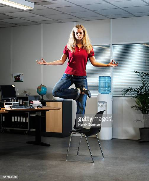 Woman meditating balancing on her office chair.