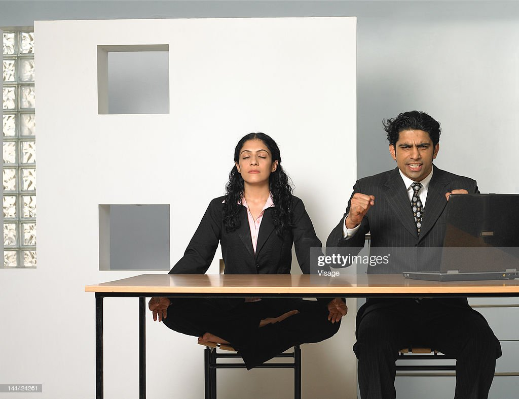 A woman meditating beside an exasperated young man, Studio shot : Stock Photo