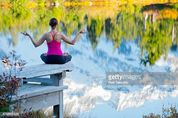 Woman meditating by lake, Bellingham, Washington, USA